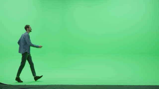 Green Screen Chroma Key Studio: Strong Handsome Smiling Man Wearing Casual Clothes Dances Across Room Left to Right. Side View Camera Shot video