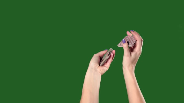 Green screen. Chromakey. Women's hands interfere with a deck of cards and throw them.