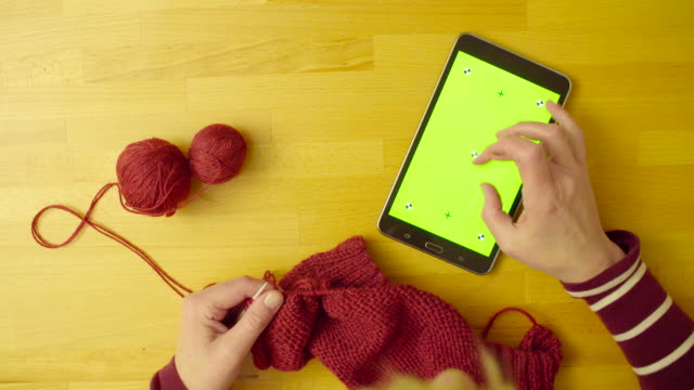 Green screen. Female hands knitting wool Top view. A tablet with green screen laying on the table. Woman's hands knitting wool and scrolling the tablet table top view stock videos & royalty-free footage