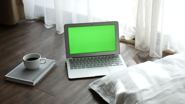 Green screen Laptop display with a book and a cup of coffee on the wood floor,Dolly shot video