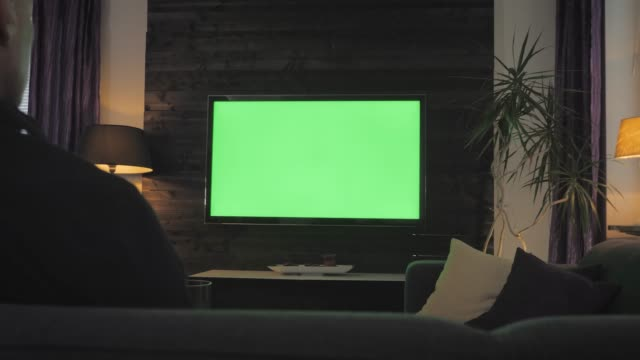 green screen-man watching tv in the living room. über die schulter schießen. - bildschirm stock-videos und b-roll-filmmaterial