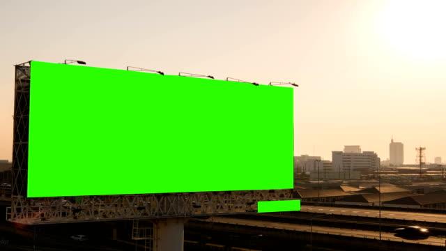green-screen von werbe-plakat auf dem expressway während des sonnenuntergangs mit stadt hintergrund in bangkok, thailand. zeitraffer. - plakat stock-videos und b-roll-filmmaterial
