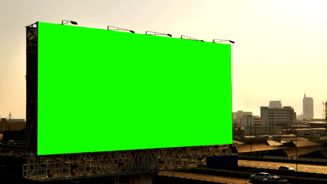 Green screen of advertising billboard on expressway during the sunset with city background in Bangkok, Thailand.