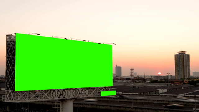 Green screen of advertising billboard on expressway during the sunset with city background in Bangkok, Thailand. Time lapse.