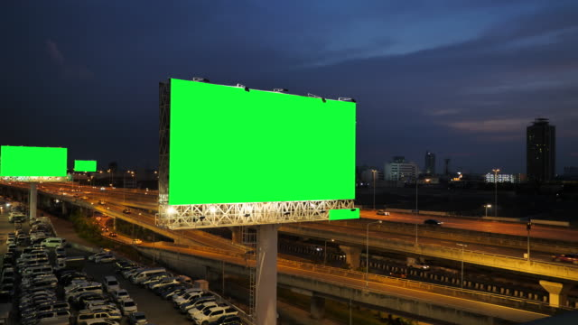 Green screen of advertising billboard on expressway during the twilight with city background in Bangkok, Thailand.