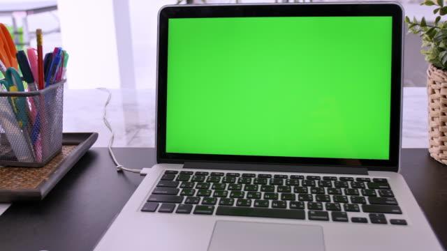 dizüstü bilgisayar 4k yeşil ekran rahat ofiste çalışma alanı üzerinde set, çekim uzaklaştırmak. - model stok videoları ve detay görüntü çekimi