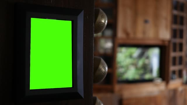 green screen picture frame hanging on pillar in living room with tv playing in background - rama obrazu filmów i materiałów b-roll