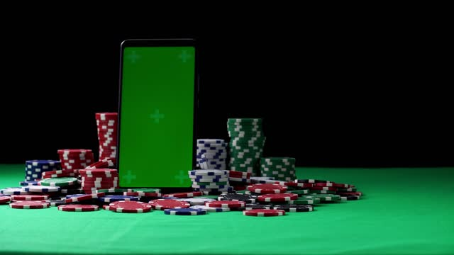 Green screen smartphone in vertical orientation in the middle of poker chips