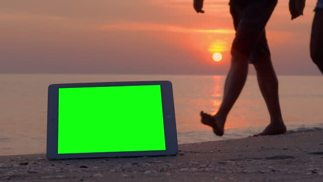 Green screen tablet computer and tracking points on the beach while tourist walking in red sunsets over sea on vacation background.Green screen on new technology concept. video