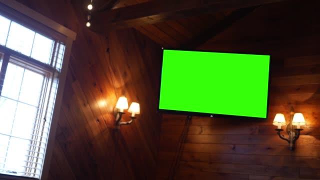 bir restoranda panelli bir duvarda yeşil ekran tv - bar stok videoları ve detay görüntü çekimi