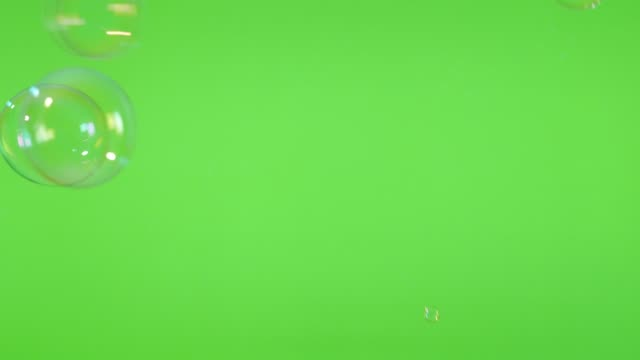 green screen with soap bubbles flying and falling down 4k 2160p 30fps ultrahd video - bubbles made of soap in front of greenscreen chroma key background 4k 3840x2160 uhd footage - mydlina filmów i materiałów b-roll