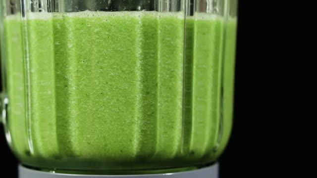 vidéos et rushes de smoothie vert mélangé dans un mélangeur, gros plan, ralenti. concept d'alimentation saine. - batteur électrique