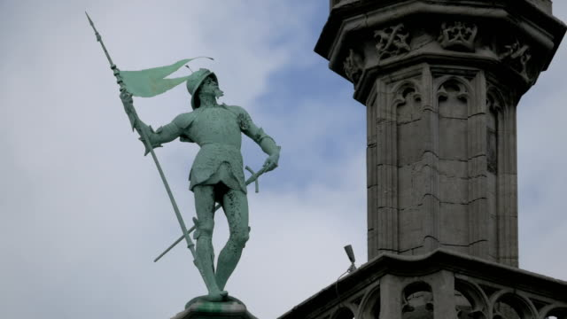 A green statue of a man in armor