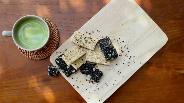 green tea is ready to drink, put together with cereal, baked white sesame and sesame seeds put on wooden plates, food for people who need health care. - sesamo video stock e b–roll
