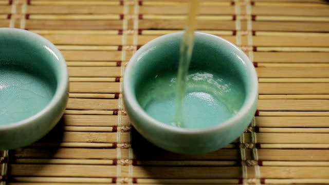 Green tea pouring into asian cup video