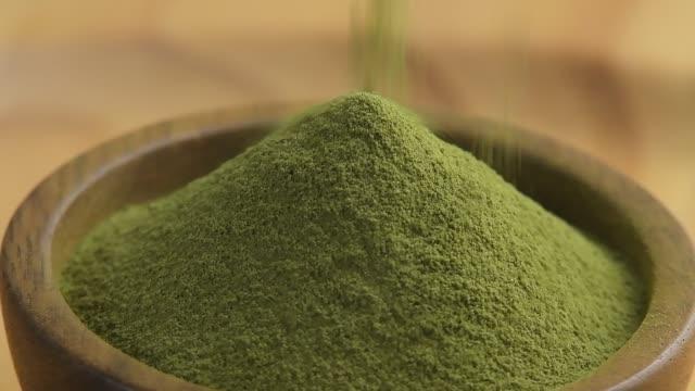 vídeos y material grabado en eventos de stock de polvo de té verde en tazón de madera - molido