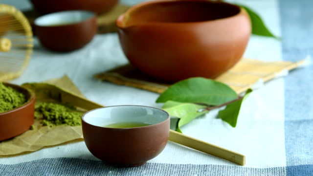 grüner tee pulver mit blatt in keramikschale auf dem tisch, japanischer drahtbesen aus bambus für matcha-tee-zeremonie. - grüner tee stock-videos und b-roll-filmmaterial