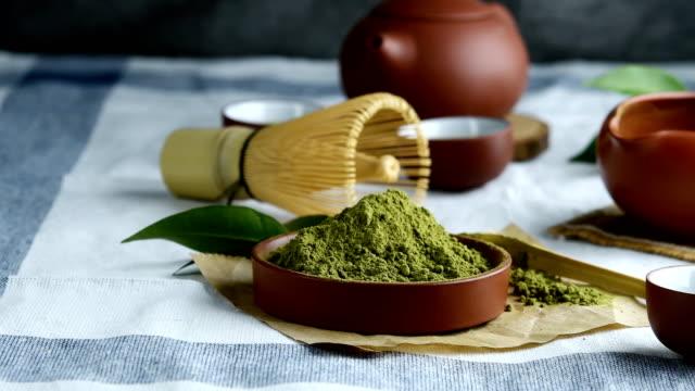 テーブルの上にセラミック皿に葉が入った緑茶パウダー、抹茶の茶道に竹で作られた和式泡立て器。 - お茶の時間点の映像素材/bロール