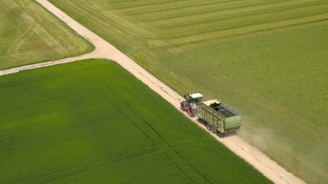 AERIAL: Green tractor driving on dusty country road between vast meadow fields video