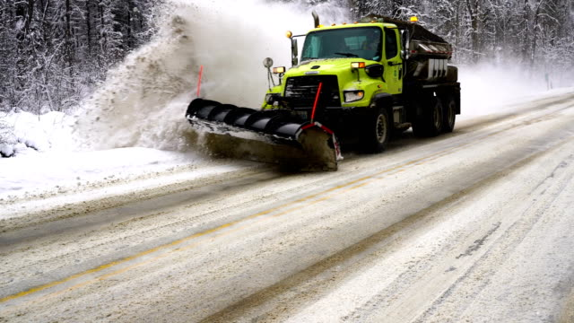 Green Truck With a Plow Displaces Snow off the Roadway Fresh snow has fallen on frozen forest roads and state workers use snow plows to move it plow stock videos & royalty-free footage