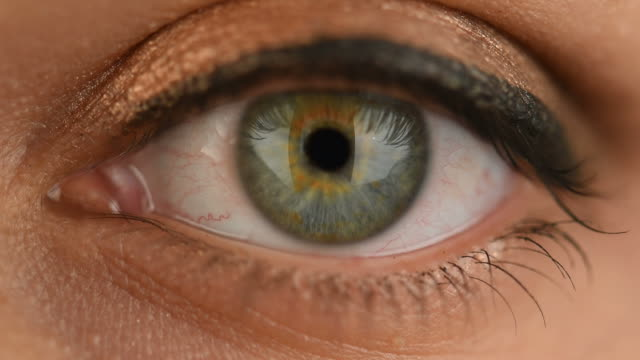 green woman eye extreme close up - battere le palpebre video stock e b–roll