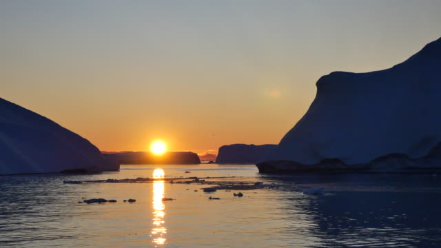 Greenland by boat, sun slides over the iceberg video