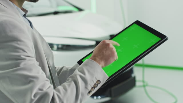 Greenscreen tablet Man standing in front of a electric car holding a tablet computer. There is a green screen on the display. alternative fuel vehicle videos stock videos & royalty-free footage