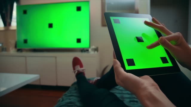 Green-Screen TV and Tablet, Scroll and Click Medium dolly shot of a caucasian woman comfortable on her living room couch, holding a tablet, scrolling down, then clicking, TV on in the background. Both on green screen with tracking marks. housing logo stock videos & royalty-free footage