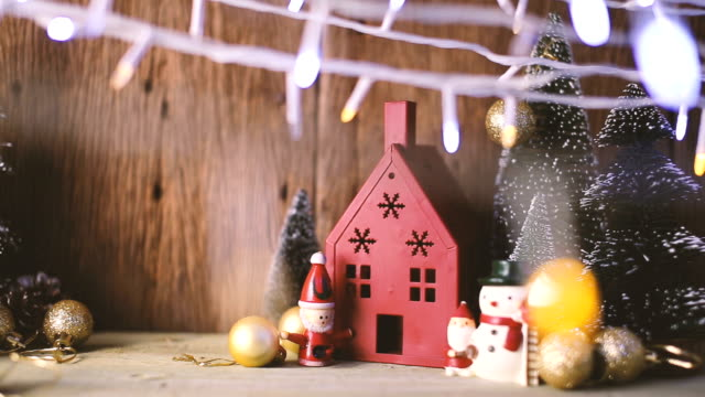 greeting season christmas and new year eve with house toy decorating items with light bokeh and pine tree on wooden table  with filter effect festive concept video