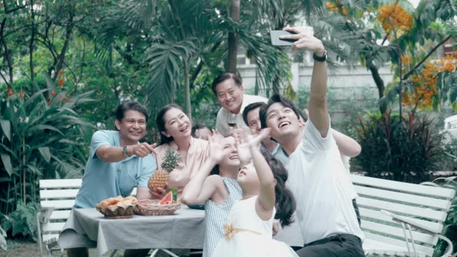 Greeting with Video conference: Thai family using phone for selfie after barbecue grill party at the front of backyard