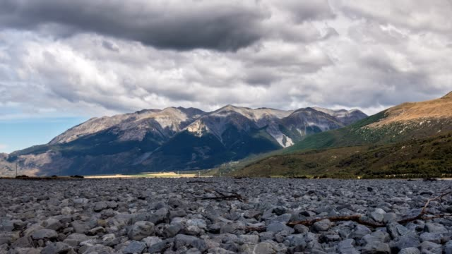 grey clouds moving over alpine mountains valley in sunny summer in new zealand wild nature time lapse - речной канал стоковые видео и кадры b-roll
