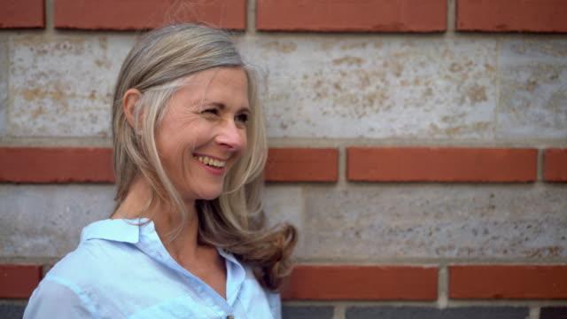 vídeos de stock e filmes b-roll de cinzento pêlo mulher madura sorridente contra uma parede texturizada - piscar