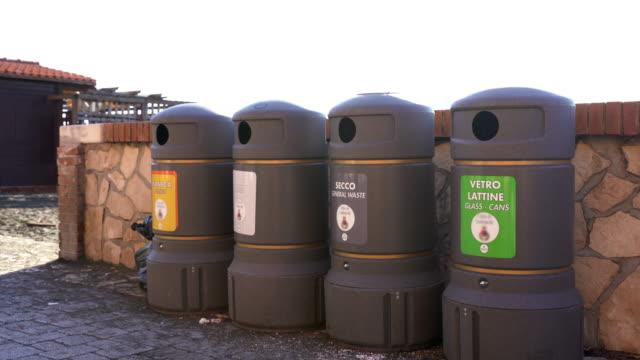 roma'da sokakta gri plastik çöp konteynerleri. daha fazla geri dönüşüm için cam, plastik, karikatür ve organik atık sıralama için özel işaretler ile çöp kutuları. roma'da çöp sorunu - dumpster fire stok videoları ve detay görüntü çekimi