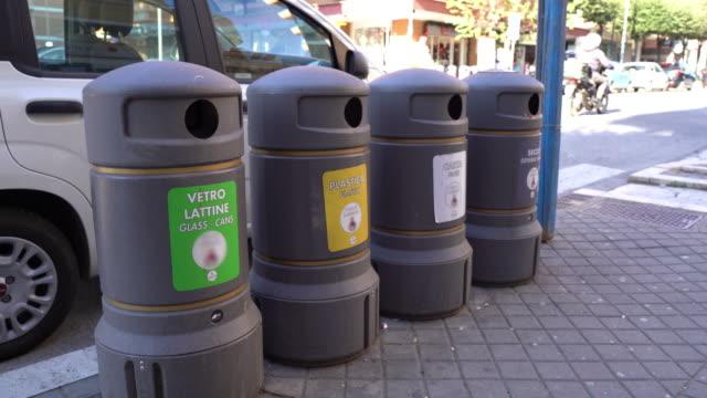 roma'da sokakta gri plastik çöp konteynerleri, daha fazla geri dönüşüm için cam, plastik, karikatür ve organik atıkları sıralamak için özel işaretler ile çöp kutuları. i̇talya'da ekolojik sorun - dumpster fire stok videoları ve detay görüntü çekimi