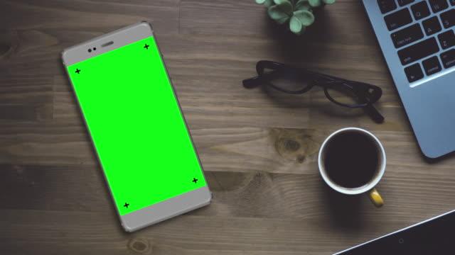 vidéos et rushes de smartphone de gris sur le bureau avec écran vert clé chroma - course poursuite