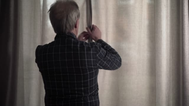 vídeos de stock e filmes b-roll de grey-haired caucasian man coming to window and opening curtains. back view of male retiree waking up in the morning at home. leisure, pension, retirement, lifestyle - old men window