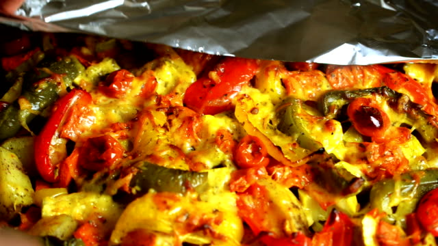 Gril colorful ecological summer vegetables, sprinkled with grated cheese in foil, expand hands and poured sauce. Multi colored vegetarian food background. video