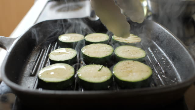 grill sliced courgette on griddle pan - zucchini video stock e b–roll
