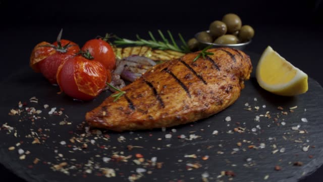 grilled chicken fillet with vegetables and spices on a black background rotation 360 degrees. 4K grilled chicken fillet with vegetables and spices on a black background rotation 360 degrees. 4K fillet stock videos & royalty-free footage