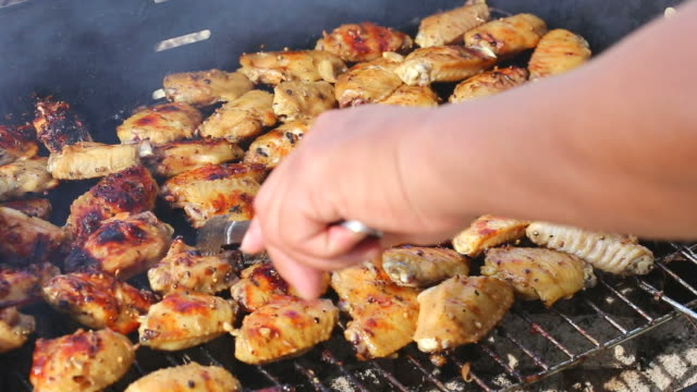 Grilled chicken thighs on the flaming grill. video