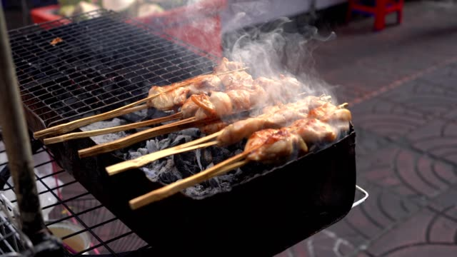 Grilled chicken with wooden stick on charcoal grill in Bangkok, Thailand Grilled chicken with wooden stick on charcoal grill in Bangkok, Thailand skewer stock videos & royalty-free footage