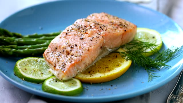 Grilled fillet of salmon with asparagus served on a plate Grilled fillet of salmon with asparagus and glass of white wine fillet stock videos & royalty-free footage