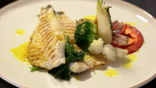 Grilled fish steak with boiled vegetables at restaurant. Grilled fish steak with boiled vegetables at restaurant. Healthy Mediterranean diet concept. Dinner at restaurant. fillet stock videos & royalty-free footage