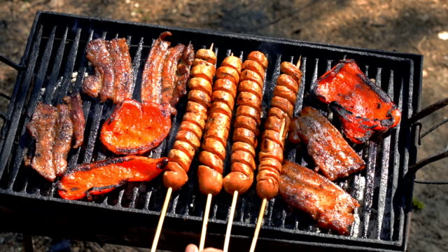 Grilled Hot Dog Sausage, Bacon and Red Peppers Over the Coals on a Barbecue - Slow Motion Grilling Meat and Vegetables. Hand Using Kitchen Tongs for Grilling Meat on the BBQ Grill. skewer stock videos & royalty-free footage