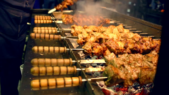 grilled meat on skewers. street food. meat rotating on skewer - spiedino video stock e b–roll