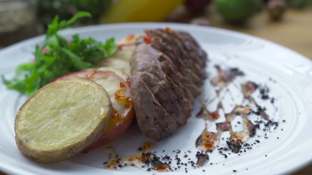 vídeos de stock e filmes b-roll de grilled meat steak with fried potatoes on white plate close up. food composition sliced meat bbq with vegetable garnish on plate. food design in high cuisine. barbecue restaurant menu - meat plate