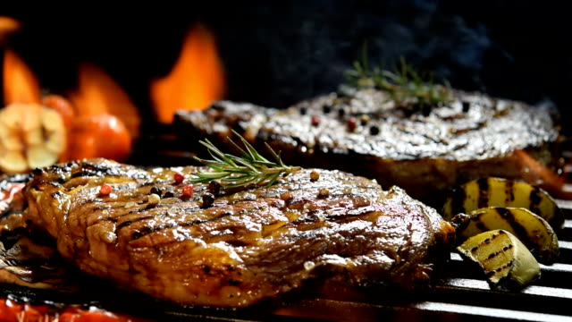 grilled meat /steak with vegetable on the flaming grill - alla griglia video stock e b–roll