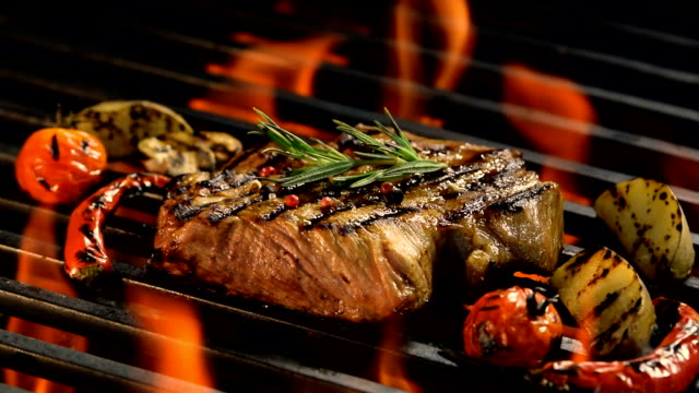 vídeos de stock e filmes b-roll de grilled meat /steak with vegetable on the flaming grill - costeleta comida
