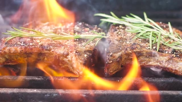 grilled meat with thyme. roast meat, sprinkled with salt and fragrant pepper. a lot of fire and smoke on the meat is a fragrant sprig of thyme. slow motion. close up.; - alla griglia video stock e b–roll
