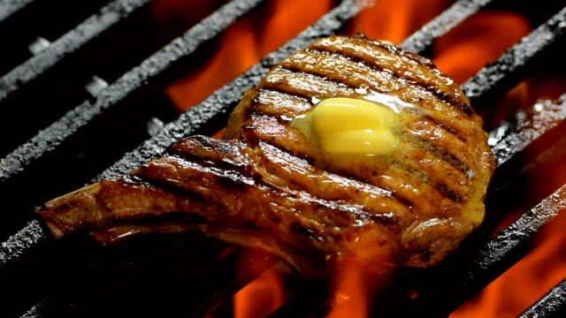 Grilled pork chop with butter on the top on Barbecue grill - fast motion video